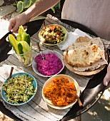 A woman serving tray of various mezze