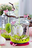 Easter table decorations with Easter eggs hanging from twigs in screw-top jars