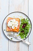 Slice of toast topped with smoked salmon and a poached egg