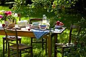 Tablett mit Geschirr auf Holztisch unter einem Apfelbaum