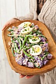A woman holding a wooden dish of purple potato salad with green beans, egg, tuna fish and mayonnaise