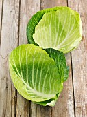 Young white cabbage leaves on a wooden surface
