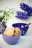 Mini doughnuts in a purple ball with snowdrops and hyacinths in the background