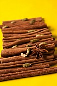Cinnamon sticks, cardamom pods and star anise on a yellow surface