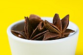 A bowl of star anise against a yellow background