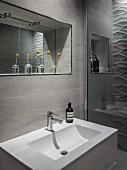 Badausschnitt - Waschbecken vor gefliester Wand, oberhalb Spiegel in Nische, davor Glasvasen mit Blumen auf Ablage