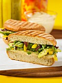 Panini with hummus, avocado, peppers and rockets