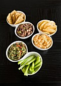 Various dips with crisps and celery sticks