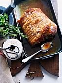 Porchetta (Italian-style roast pork) in a roasting tin