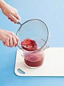 Raspberry purée being sieved
