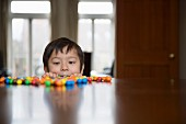 A boy peering over the edge of a table at sweets