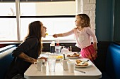 A little girl feeding her mother in a restaurant