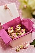 Cupcakes topped with white chocolate and sugar roses as a gift