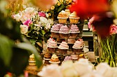 Various cupcakes on a cake stand surrounded by flowers