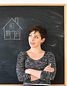 A woman in front of blackboard with a drawing of a house