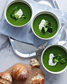 Three bowls of broccoli soup with sour cream