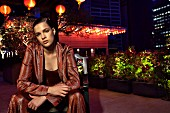 Frau in Glitzertop, Glitzerblazer und Glitzerhose in Kupferfarben, braun, sitzt auf Stuhl