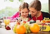Zwei Schwestern schneiden frisches Obst auf Terrassentisch