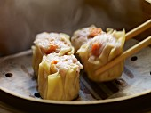 Siu Mai Dim Sum (Cantonese pork and prawn dumplings) one being lifted with chop sticks