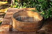 Altes Mehlsieb auf Holztisch im Garten