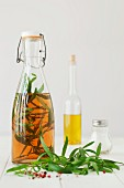 A bottle of tarragon vinegar, fresh tarragon and peppercorns