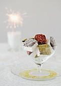 Chocolate-covered, coated marshmallows in a glass bowl with a sparkler in the background