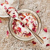 Rose scented sugar in a glass bowl with a spoon on a silver tray