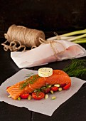 Salmon fillet with dill butter, tomatoes and spring onion on parchment paper