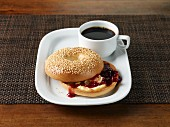 A sesame seed bagel with butter and jam served with coffee