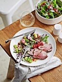 Glazed roast lamb with herb flowers and redcurrants
