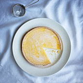 Lemon tart with icing sugar, sliced (seen from above)