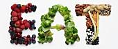Schriftzug EAT aus Beeren, Gemüse, Hülsenfrüchten und Erdnüssen