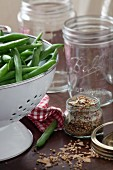 Fresh green beans in a white colander and herbs for pickling
