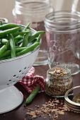 Frische grüne Bohnen in weißem Küchensieb und Gewürze zum Einlegen