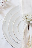 A white place setting decorated with apple blossom on a wedding party table