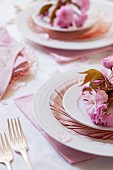 Pink cherry blossoms on place settings at a wedding party (close-up)