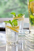 Lemon water with mint in two glasses and a jug