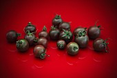 Dark cherry tomatoes on a red surface