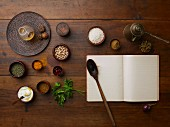 Various spices, chickpeas, rice, parsley and a blank cook book with a wooden spoon