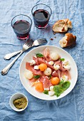 Melon with Prosciutto and mozzarella served with red wine and baguette