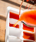 Tomato juice being poured into an ice cube tray to be frozen