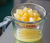 Diced pineapple in a sieve over a measuring jug