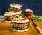 Hamburger mit Käsefüllung, Tomaten, Zwiebeln und Salat