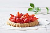 A strawberry tartlet on a doily
