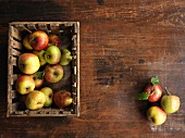 Fresh organic apples in a wooden crate on a wooden surface