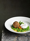 Breaded black pudding with a poached egg and peas