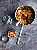 Pear chutney in a saucepan and a preserving jar
