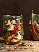 Pickled mushrooms with chilli peppers and herbs