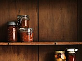 Various preserving jars on a wooden shelf