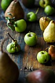 Various organic apples and pears on a wooden surface